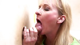 Horny blonde matured puts a penis deep inside her trough the wall